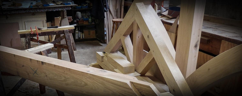 An oak building frame under construction in the workshop